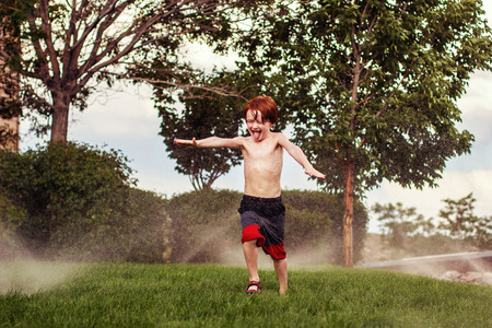 seven year old redhead boy running through the sprinklers in the summer