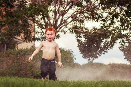 three year old redhead boy playing in the sprinklers in the summer