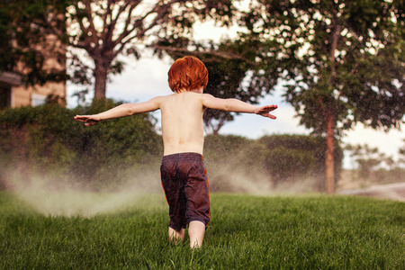 four year old redhead boy running in the sprinklers on a hot summer day
