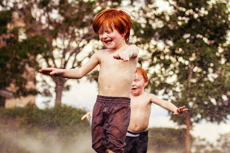 redhead brothers playing in the sprinklers