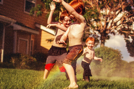 three redhead brothers playing in the sprinklers on a hot summer day