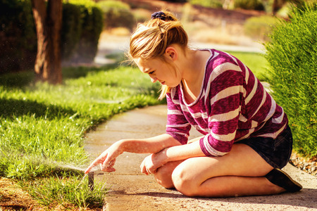 preteen girl sitting on the sidewalk playing with sprinklers