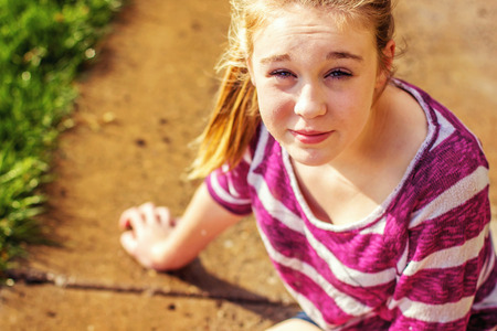 preteen girl sitting on the wet sidewalk