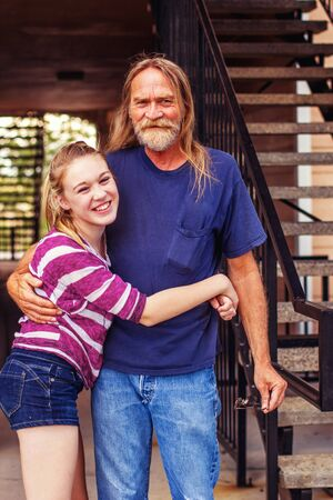 grandfather getting a hug from his preteen granddaughter Stock Photo