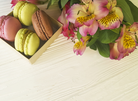Macaroon in a box on a white wooden background, alstroemeria flower