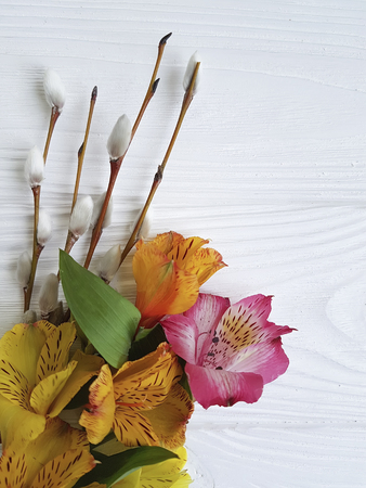 willow, flowers on a white wooden background with alstroemeria Stock Photo