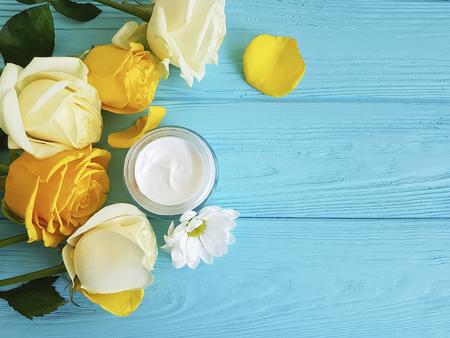 cosmetic cream, yellow rose on blue wood