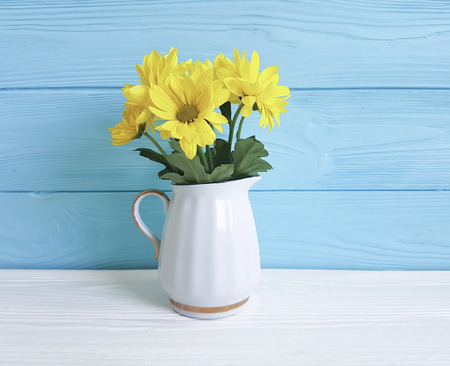 yellow chrysanthemum vase on white and blue
