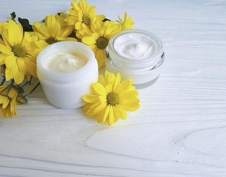 cosmetic cream in a jar yellow chrysanthemum white wooden