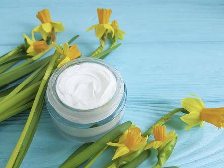 cream cosmetic yellow flowers blue wooden background daffodil Foto de archivo