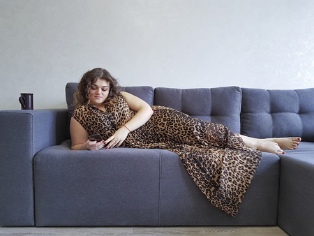 beautiful full girl lying on the couch phone, cup, dress, dreams