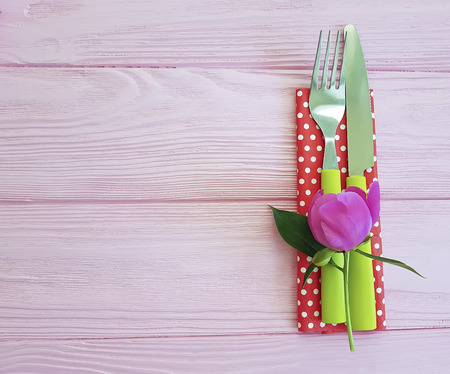 fork peony flower knife on a pink wooden background