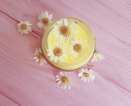 cream cosmetic daisy on a wooden background