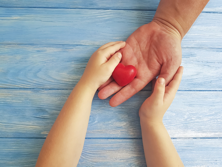 Father's Day Hands Dad and Child's Heart on a Blue Wooden Background