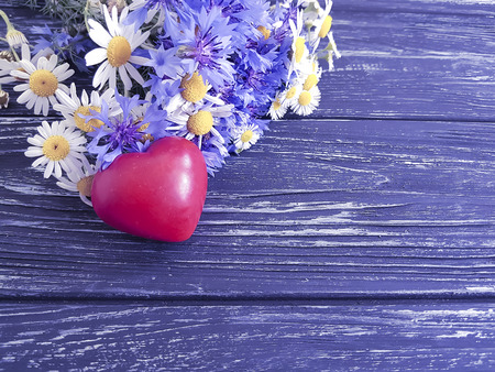 bouquet of cornflowers, chamomile heart, on a wooden background