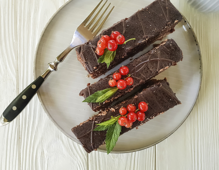 chocolate cake, red currant, mint plate on white wooden Imagens