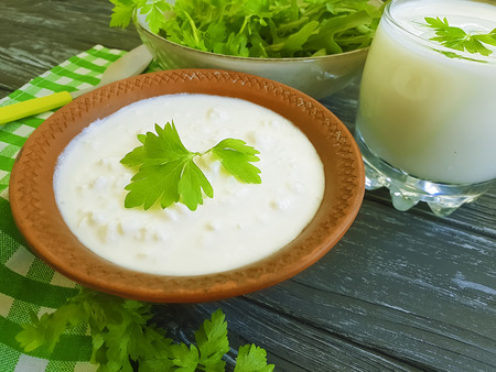 cottage cheese, yogurt parsley greens on a black wooden background