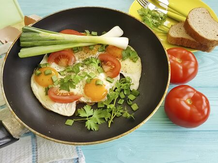 fried eggs tomato in pan on wooden background