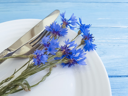 flowers cornflowers, plate, fork knife on a wooden background Imagens