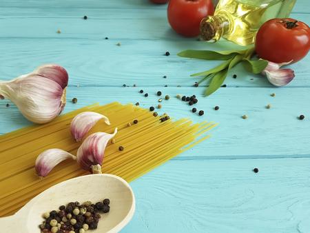 spaghetti, tomato, garlic on a blue wooden background Imagens