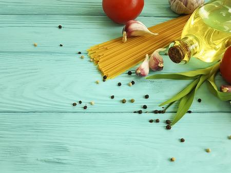 spaghetti, tomato, garlic on a blue wooden background