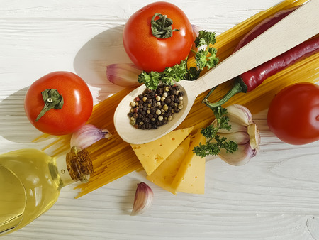 spaghetti, tomato, garlic, pepper, butter, cheese on a wooden background Imagens