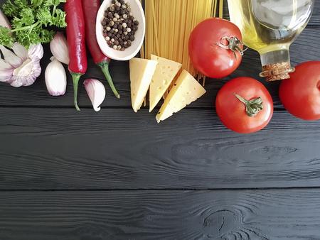 spaghetti, tomato, garlic, cheese on a black wooden background