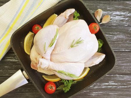 chicken damp, whole in frying pan on dark wooden background Banco de Imagens