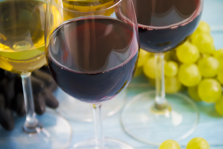 glass of wine, green and blue grapes on a wooden background