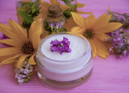cream cosmetic essence, cosmetic, oil, flowers on a wooden background