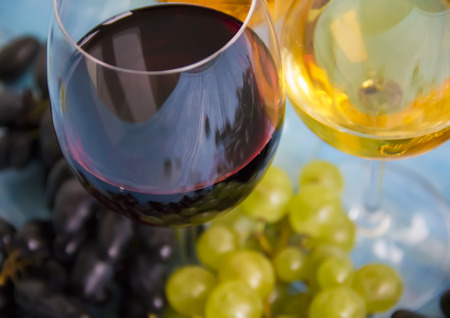 Glass of wine, fresh grapes on a blue background