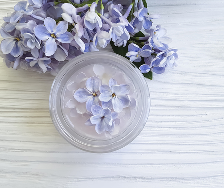 cosmetic cream, lilac flower on a white wooden background Reklamní fotografie