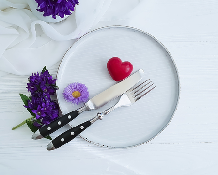 plate, fork, knife, heart, chrysanthemum flower on white wooden background