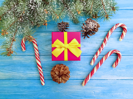 candy box, christmas tree branch, gift box on a blue wooden background