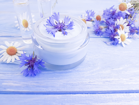 cosmetic cream, chamomile flower, cornflower on a wooden background