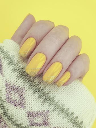 female hand manicure yellow sweater Stok Fotoğraf