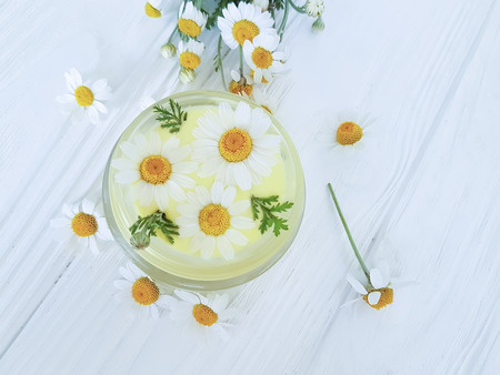 chamomile flower, cosmetic cream on a wooden