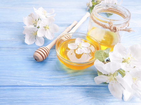 fresh honey, blooming apple tree, wooden background