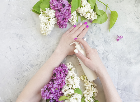 female hands manicure, cream cosmetic lilac flower Stockfoto
