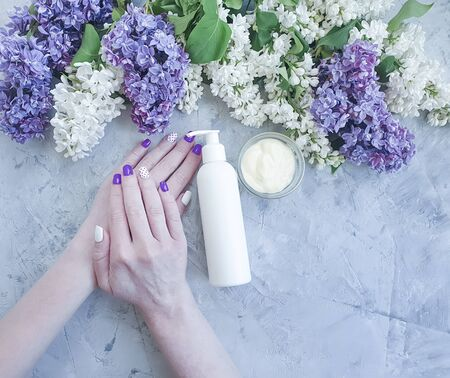 female hands manicure cream flower lilac