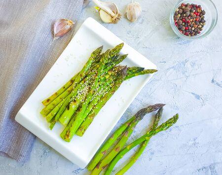 fried asparagus, sesame seeds on a gray concrete Zdjęcie Seryjne - 129255626