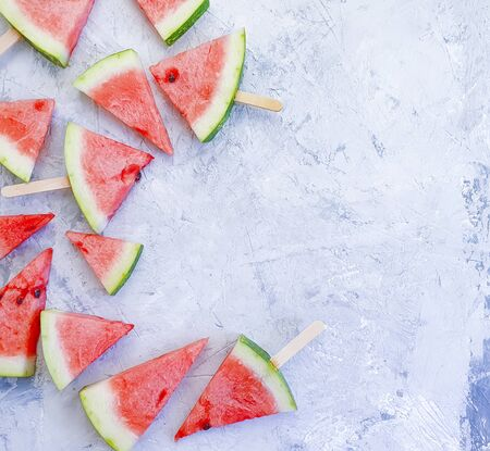 slices of watermelon on a gray concrete