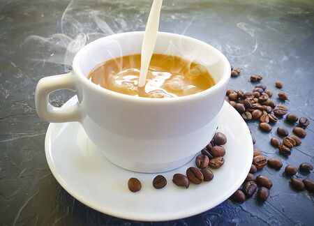 milk is poured into a cup of coffee
