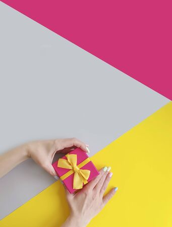 female hands holding a gift box on a colored background