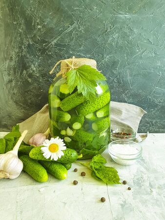 pickles in a jar, garlic on a concrete