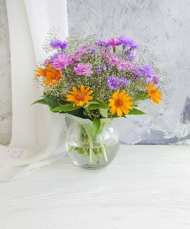 summer flowers in a vase on a concrete