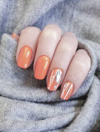 female hand beautiful orange manicure