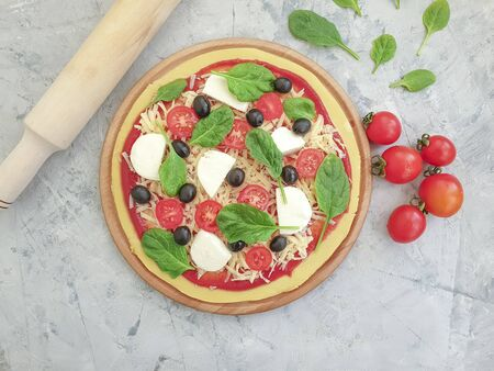 pizza, tomatoes, olives on concrete background preparation