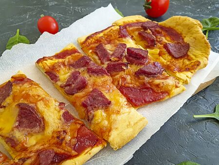 baked pizza with sausage on a concrete background 写真素材
