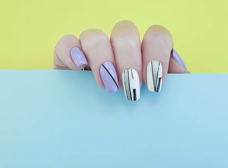 female hand nails beautiful manicure on color paper Imagens